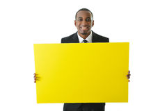 Businessman Holding Big Yellow Board. Business man holding a big yellow board to be filled in with any idea or concept Royalty Free Stock Image