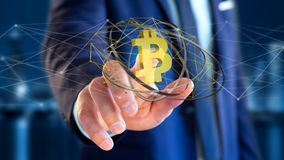 Businessman holding a Bitcoin crypto currency sign flying around. View of a Businessman holding a Bitcoin crypto currency sign flying around a network connection Royalty Free Stock Images
