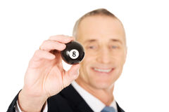 Businessman holding black billiard ball Royalty Free Stock Photography