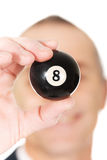 Businessman holding black billiard ball Stock Images