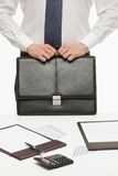 Businessman holding a black briefcase and standing near the work Royalty Free Stock Photo