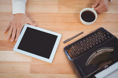 Businessman holding black coffee with typewriter and digital tablet Royalty Free Stock Images
