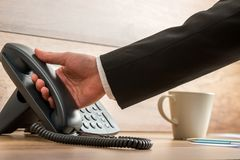 Businessman holding black landline telephone handset to pick it up from the base to answer a phone call. With coffee mug stock photos