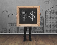 Businessman holding blackboard with hand-drawn ideas equal money. Concept on cityscape doodles wall and teak wooden floor background royalty free stock photos