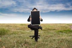 Businessman holding a blackboard. Stock Image