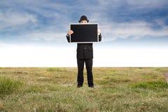 Businessman holding a blackboard. Royalty Free Stock Image