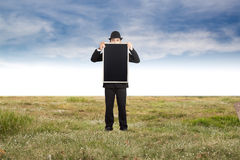 Businessman holding a blackboard. Stock Images