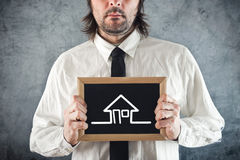 Businessman holding blackboard house drawing Stock Image