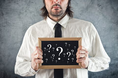 Businessman holding blackboard with question marks. Business questioning Royalty Free Stock Photos