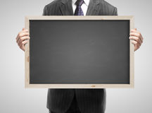 Businessman holding blackboard Royalty Free Stock Photography