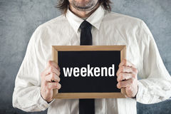 Businessman holding blackboard with WEEKEND title Stock Images