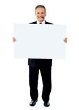 Businessman holding a blank billboard Royalty Free Stock Photos