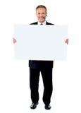 Businessman holding a blank billboard Royalty Free Stock Photos