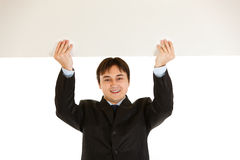 Businessman holding blank billboard over head Stock Photography