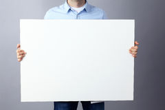 Businessman holding a blank board on gray background Royalty Free Stock Image