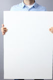 Businessman holding a blank board on gray background Royalty Free Stock Images