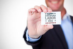 Composite image of businessman holding blank card against white background. Businessman holding blank card against white background against happy labor day text Stock Photo