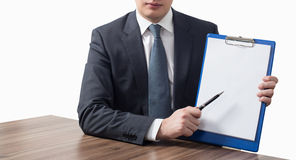 Businessman holding blank clipboard. Young businessman in suit holding blank clipboard Stock Photo