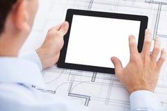 Businessman holding blank digital tablet over blue Royalty Free Stock Images