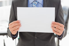 Businessman holding blank page. In the office Stock Image
