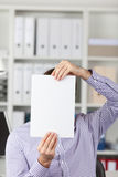 Businessman Holding Blank Paper In Front Of Face In Office Royalty Free Stock Photography