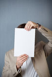 Businessman Holding Blank Paper In Front Of Face Stock Image