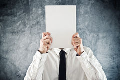 Businessman holding blank paper in front of his face Royalty Free Stock Photo