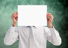 Businessman holding blank placard in front of his face against green background Stock Photos