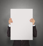 Businessman holding blank poster on texture wall Royalty Free Stock Photography