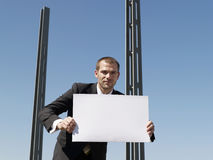 Businessman Holding Blank Sheet By Concrete Pillars Royalty Free Stock Photography