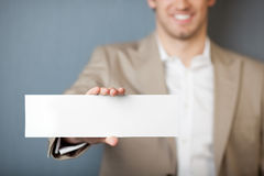 Businessman Holding Blank Sign Against Blue Wall Royalty Free Stock Photos