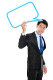 Businessman holding blank text bubble over head Stock Photo