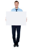 Businessman holding blank white billboard Stock Images