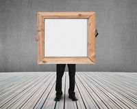Businessman holding blank white board with wooden frame indoors Stock Image