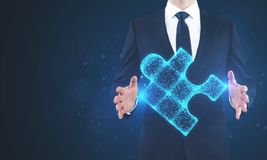 Businessman holding blue puzzle. Businessman holding glowing blue puzzle on blurry background. Future and innovation concept Stock Photo