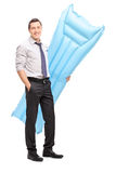 Businessman holding a blue swimming mattress. Full length portrait of a young businessman holding a blue swimming mattress and looking at the camera isolated on royalty free stock photography