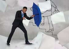Businessman holding blue umbrella amidst flying papers against graffiti wall Stock Photography