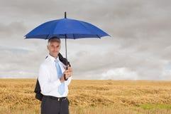 Businessman holding blue umbrella. Composite image of mature businessman holding blue umbrella Royalty Free Stock Photos