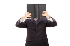 Businessman holding a book in front of his face Stock Image