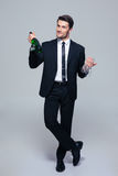 Businessman holding bottle with champagne and glass Stock Photos