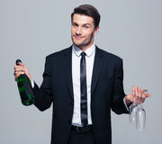 Businessman holding bottle with champagne and glass Stock Photo