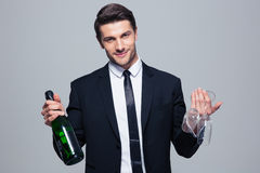 Businessman holding bottle with champagne and glass Royalty Free Stock Photo