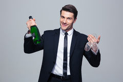 Businessman holding bottle with champagne and glass Stock Images