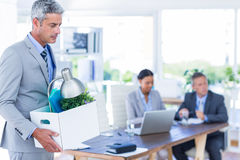 Businessman holding box with his colleagues behind him Royalty Free Stock Images