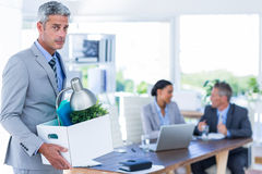 Businessman holding box with his colleagues behind him Stock Image