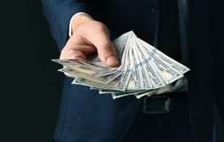 Businessman holding bribe. On black background Royalty Free Stock Photography