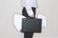 Businessman holding briefcase. Businessman holding a briefcase stuffed with papers coming out Stock Image