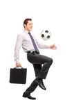 Businessman holding a briefcase and juggling a football Stock Images