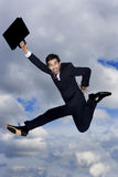 A businessman holding a briefcase, leaping in the air royalty free stock images