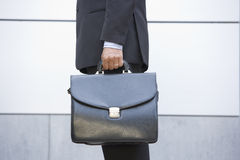 Businessman holding briefcase outdoors Royalty Free Stock Photography